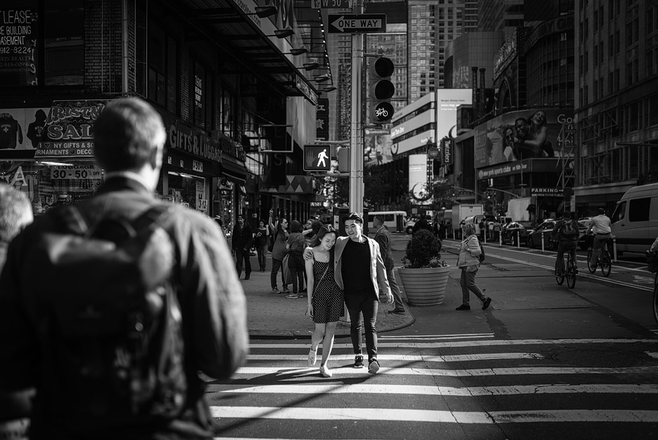 New York City black and white street photo of couple crossing the road