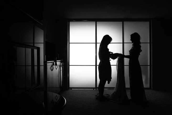 Silhouette of bride getting into dress