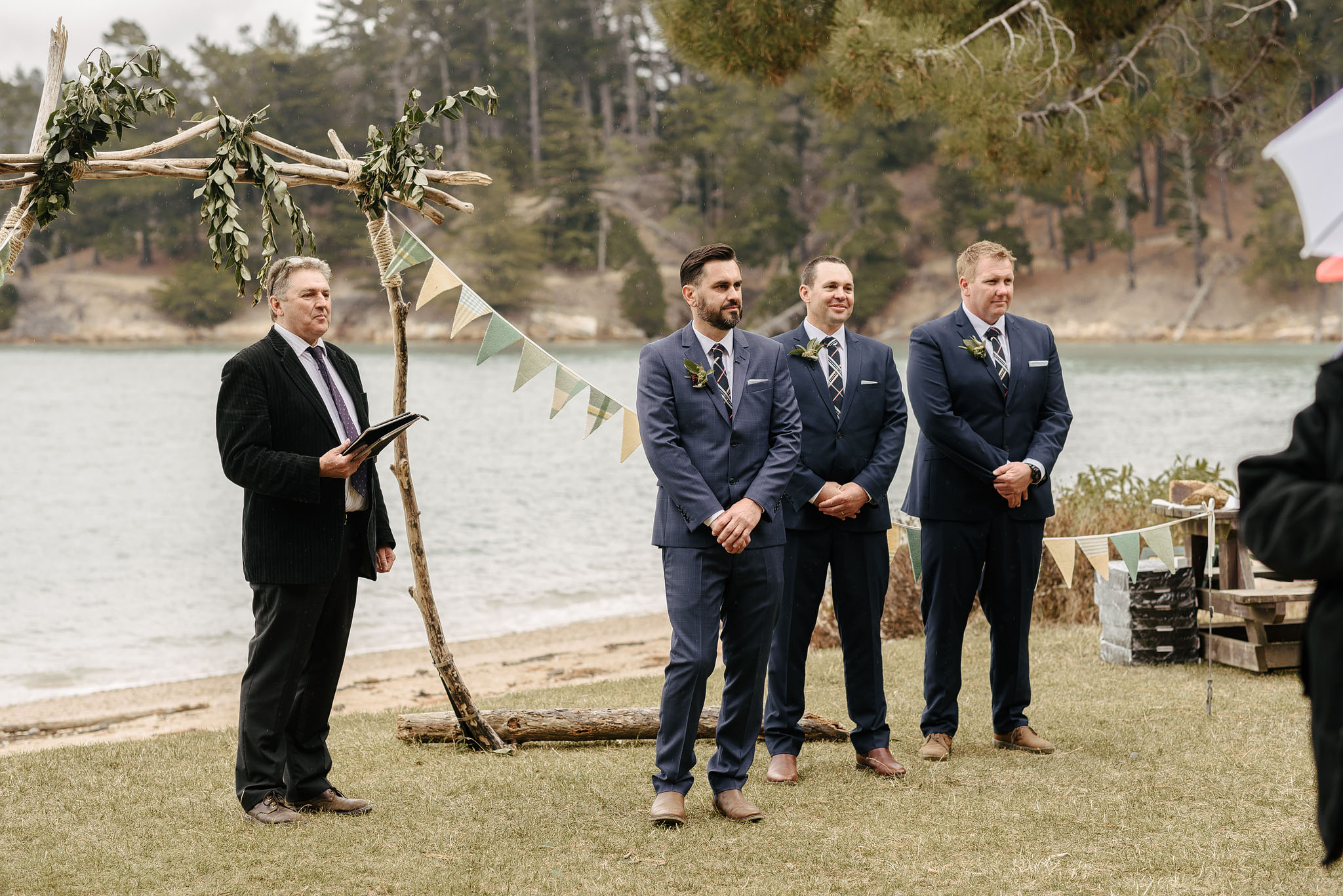 Celebrant John Sellwood with groom and groomsmen as bride arrives at Christchurch wedding
