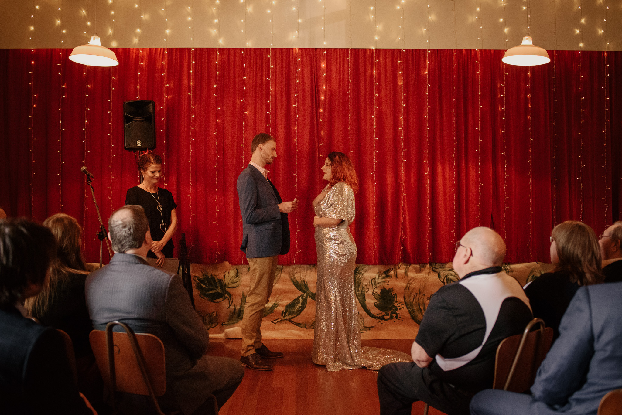 Emotional ceremony in front of red curtain at Ohoka Hall