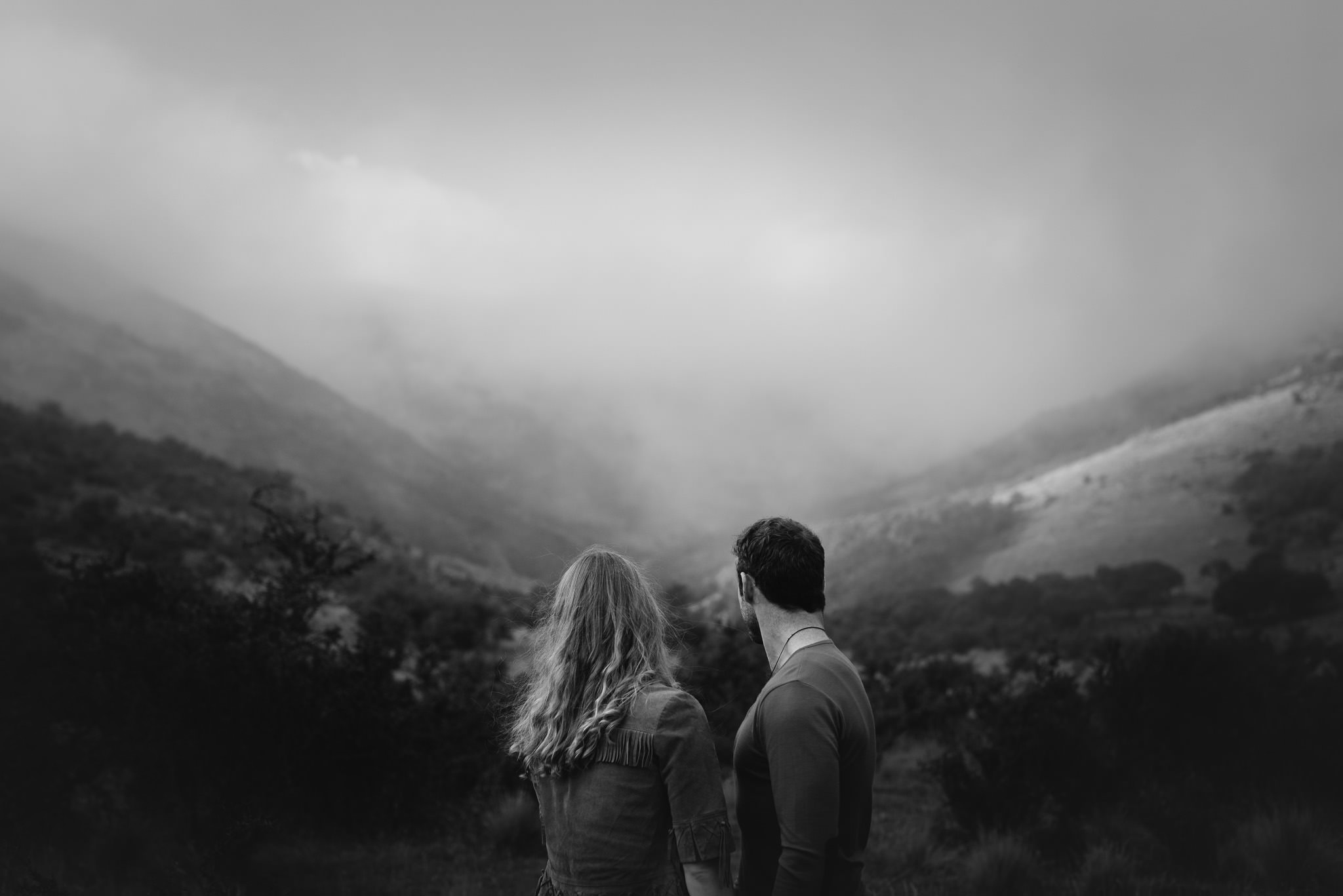 Black and white photo of couple looking away from camera towards misty hills