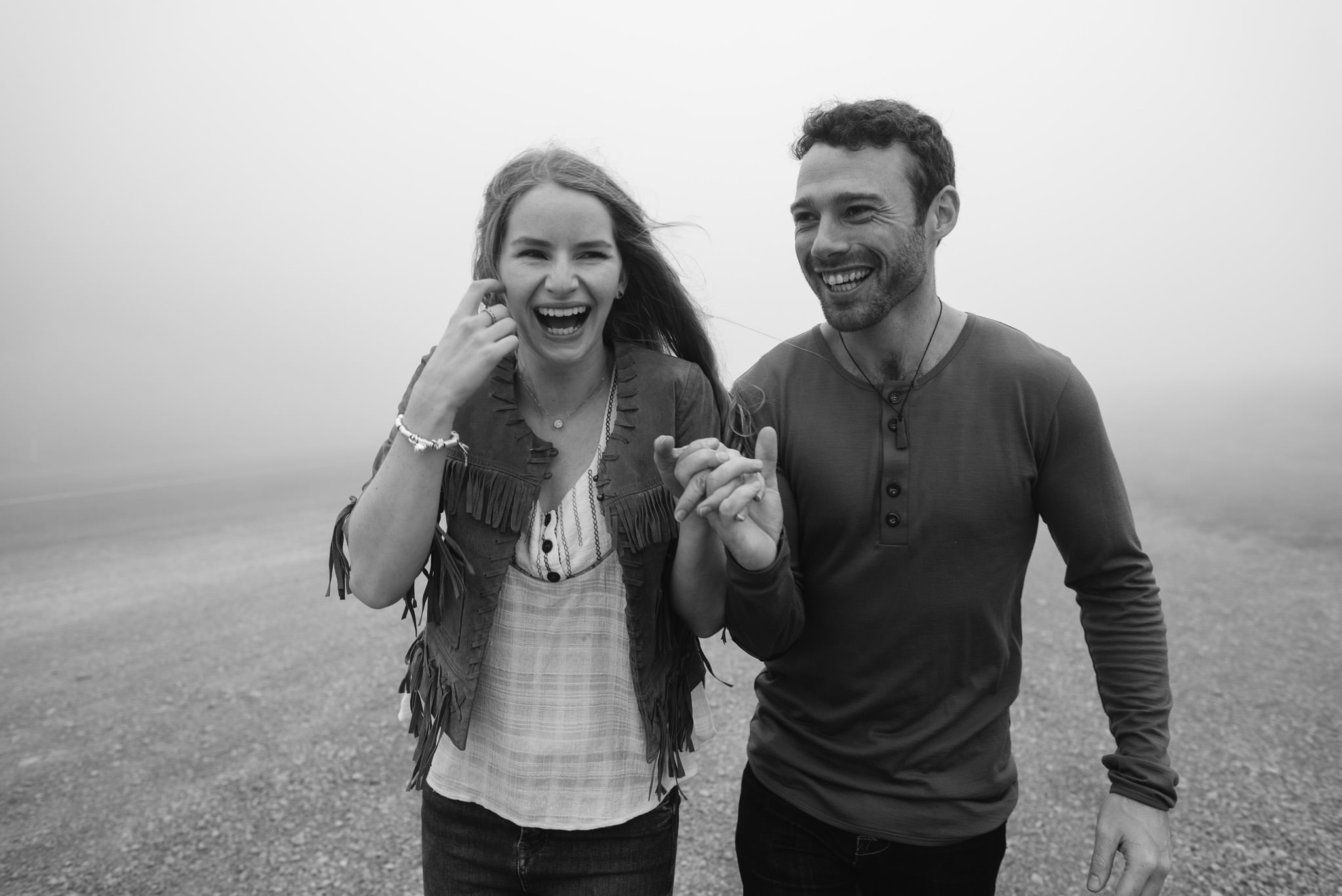 Couple in black and white walking through fog