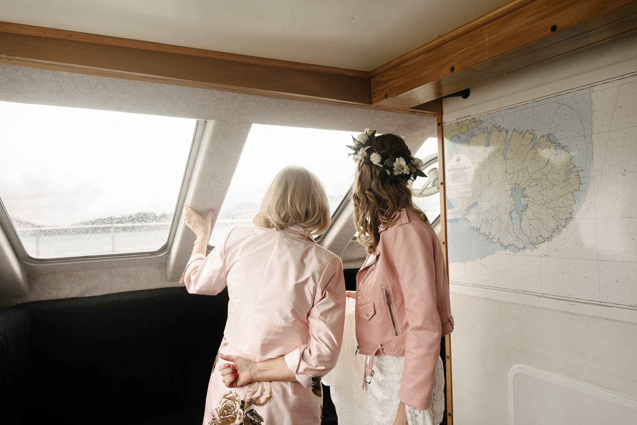 Bride in pink leather jacket and Rue de Seine wedding dress, on boat to Quail Island