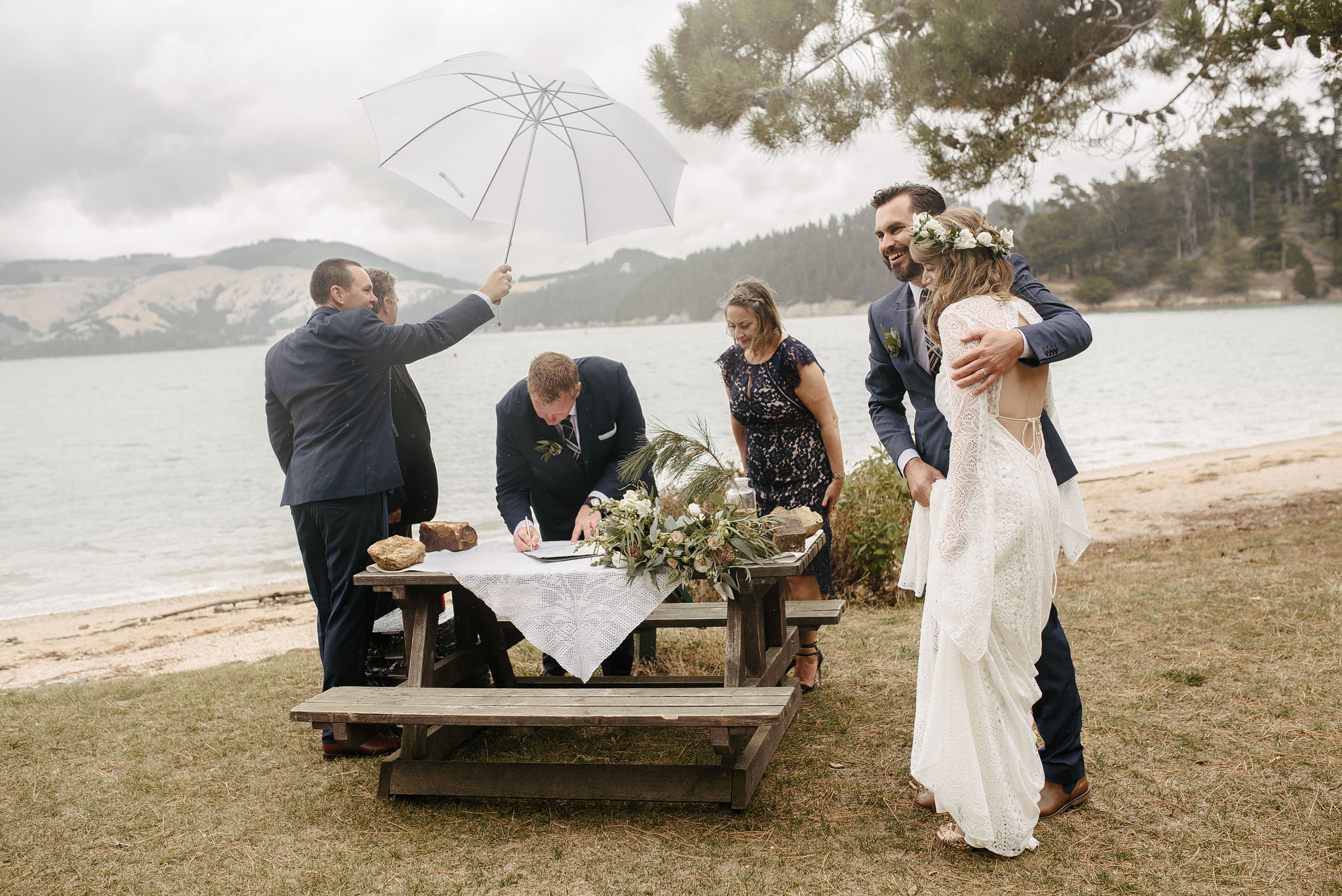 Hugs during signing of the register at a beach wedding in Lyttelton harbour