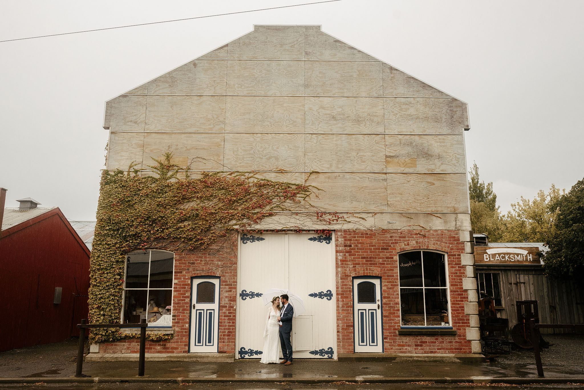 Under umbrella - rainy New Zealand wedding